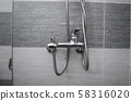 Modern designer tap and shower in bathroom. Closeup of chrome shower, faucet, in the bathroom 58316020