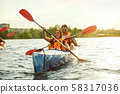 Happy couple kayaking on river with sunset on the background 58317036