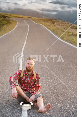 Stylish barefoot bearded male hitchhiker traveler in a hat and with a backpack sits on a suburban 58317049