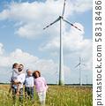 Multigeneration family standing on field on wind farm. 58318486