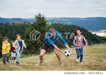 Group of school children with teacher on field trip in nature, playing with a ball. 58318612
