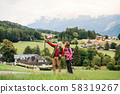 Senior pensioner couple with nordic walking poles hiking in nature, talking. 58319267