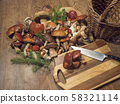 Assorted edible mushroom Boletus close up on wooden rustic table with wicker basket, cutting board 58321114