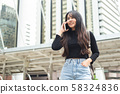 Asian young woman talking telephone in city. 58324836
