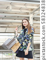 Portrait beautiful woman stand holding shopping bags in city center. 58324838