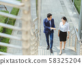 Businesswoman and businessman with tablet walking talk about work outdoor place. 58325204