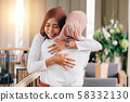 Portrait of young Asian muslim women in happy smile with hijab or head scarf hugs each other indoors 58332130
