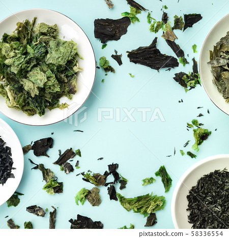 Various dry seaweed, sea vegetables, square overhead shot on a teal background forming a frame with 58336554