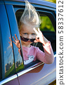 A child in sunglasses rides and smiles in a car 58337612