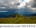 Storm clouds and sun rays over the mountains 58339342