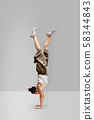 Young woman is practicing yoga, doing handstand exercise, with grey background, vertical photo 58344843