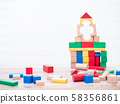 Building wooden blocks by children on table and white bricks wall background with copy space. 58356861