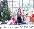 Beautiful woman and two little girl holding a confetti and very happy in Christmas cerebration. 58356865