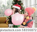 Portrait of two happy little girl blasting balloon at home with Christmas tree decoration. 58356872