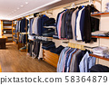 Fashion modern men clothes displayed on shelves and hanger racks in clothing store 58364879