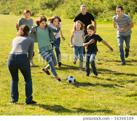 Glad males and females kicking the ball 58366389