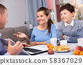 Happy family communicating over breakfast at home in morning 58367029
