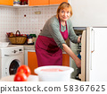 Mature housewife takes food out of the fridge in the kitchen 58367625