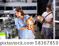 Woman with dog with interest looking at small aquarium 58367859