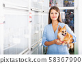 attractive woman with dog walking in pet store near birdcages 58367990