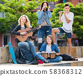 Teenagers friends playing musical instruments 58368312