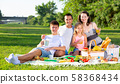 Happy young parents with two teenagers having a picnic on the countryside 58368434