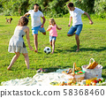 Group of smiling children and parents having fun together outdoors playing football 58368460