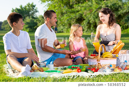 Parents with two teenagers enjoying delicious meal on the picnic 58368552