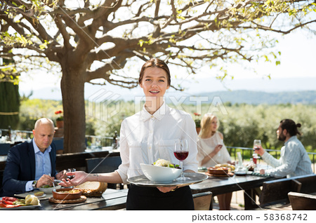 Female owner of country restaurant in open air meeting guests 58368742