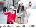 Cheerful woman with daughter making selfie 58369001