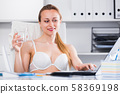 Cheerful woman in bra working 58369198