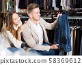 Couple examining various trousers 58369612