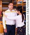Chinese woman tailor using measurement tape with client in mens cloths store 58370064