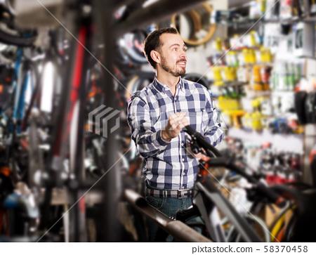 Man considers bicycle handlebar in store 58370458
