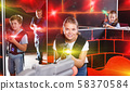 Excited girl aiming laser gun near other players during laser ta 58370584