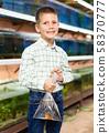 Boy with aquarium fish in plastic bag 58370777