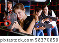 Portrait of exciting girl with laser pistol playing laser tag in dark room 58370859
