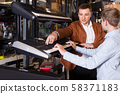 Father and teenage son examining keyboards in guitar shop 58371183
