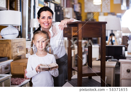 Woman with girl in furniture store 58371655