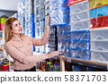 Modern female buying plastic storage containers 58371703