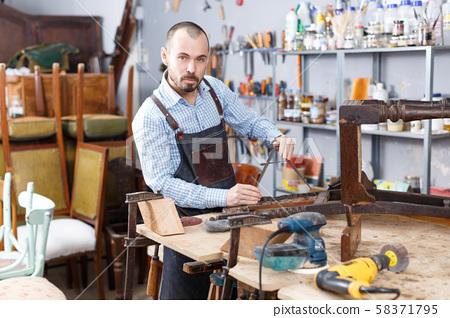Carpenter repairing antique chair 58371795