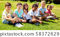 Group of elementary school children chatting on the green lawn 58372629