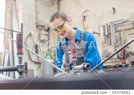 woman in Metal workshop with tools and workpiece 58378881