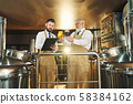 Two specialists analyzing light and dark beer in brewery. 58384162