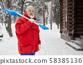 Grandfather keeping shovel in shoulder and smiling in winter 58385136