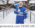 Man with shovel on shoulder looking at camera in winter 58385180