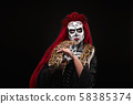 Woman with sugar skull make up holding serpent. 58385374