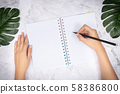 flat lay of woman hand writing in a blank white page notebook on white marble desk, top view. green palm leaf on desk for decoration 58386800