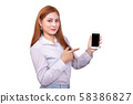 smiling Asian woman standing in casual shirt holding mobile phone and  pointing on smartphone isolated on white background with clipping path 58386827