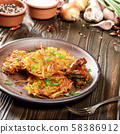 Homemade tasty potato pancakes in clay dish with 58386912